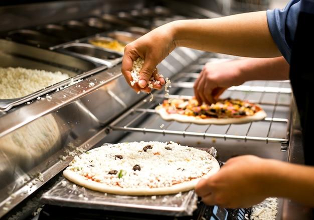 Chefkoch legt käse auf pizzateig mit tomatensauce bedeckt