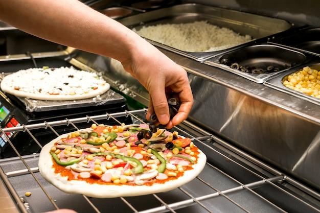 Chefkoch legt oliven auf pizzateig mit tomatensauce bedeckt