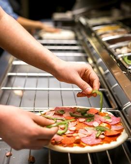 Chefkoch legt pfeffer auf pizzateig mit tomatensauce bedeckt