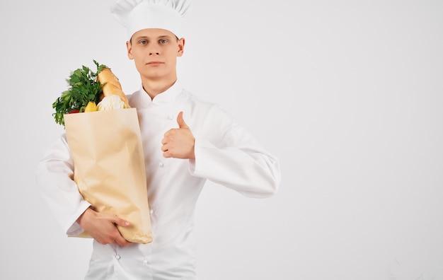 Chefkoch mit einem lebensmittelpaket im professionellen restaurant für die zubereitung von speisen
