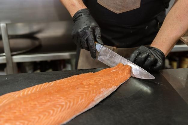 Chefkoch mit schwarzen hygienehandschuhen, die einen riesigen frischen lachs reinigen und zubereiten. entfernen und schälen der haut vom fisch. küchen- und lebensmittelkonzept