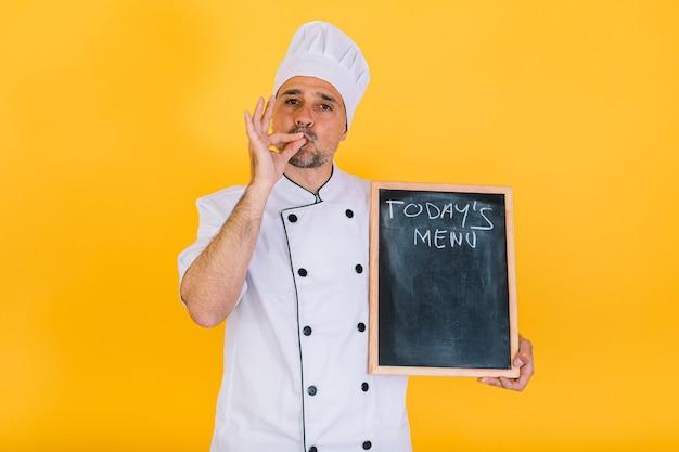 Chefkoch mit weißem küchenhut und jacke hält eine tafel mit der aufschrift