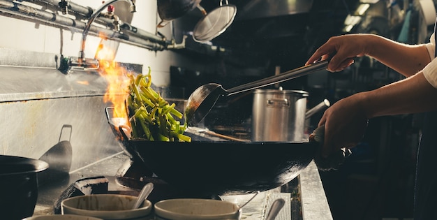 Chefkoch rühren braten beschäftigt kochen in der küche. chefkoch rühren braten das essen in einer pfanne, rauchen und die sauce in der küche bespritzen.