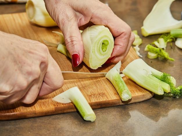 Chefkoch schneidet den fenchel nach dem kochrezept auf holzbrett in der küche.