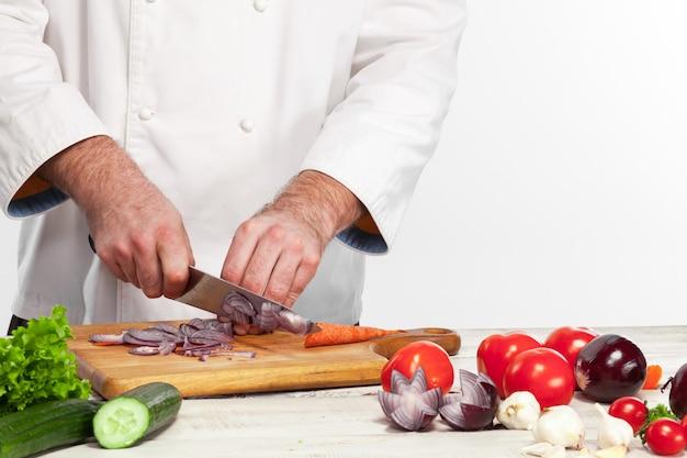 Chefkoch schneidet eine zwiebel auf seiner küche