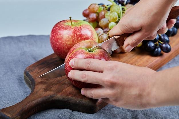 Chefkoch schneidet einen roten apfel mit einem messer auf dem brett.