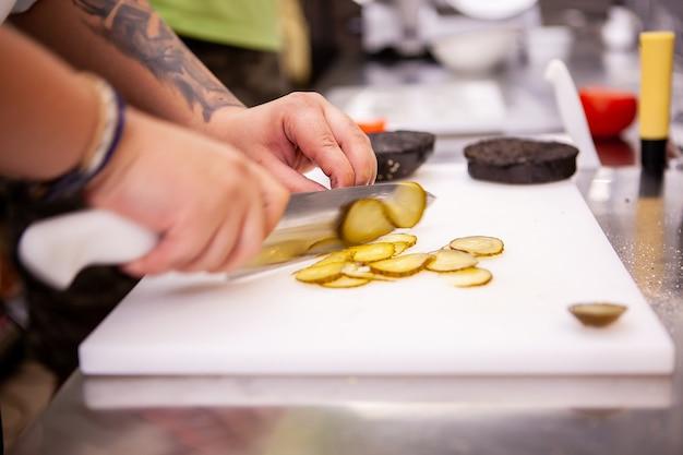 Chefkoch schneidet essiggurken für leckeren burger im restaurant. essenszubereitung