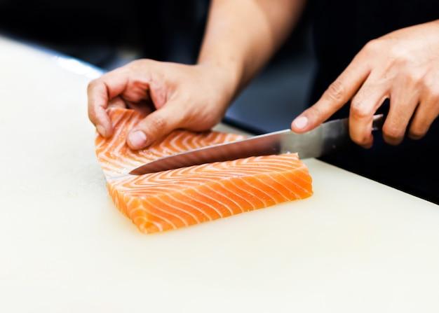 Chefkoch schneidet lachsfilet mit einem messer in scheiben, chefkoch schneidet den lachs im restaurant