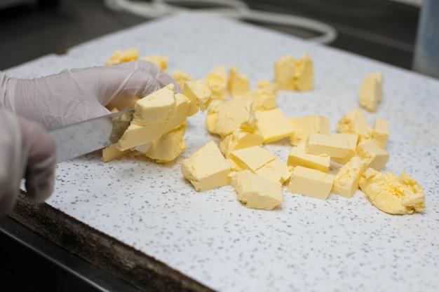 Chefkoch schneidet ungesalzene butter in stücke.