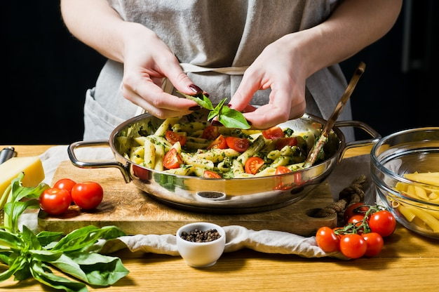 Chefkoch streut basilikumblätter auf pasta penne.