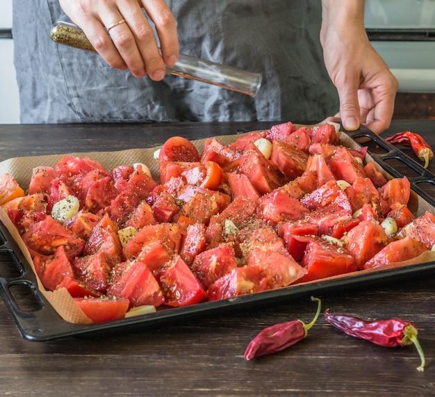 Chefkoch streut gewürze oder trockene kräuter der glaskolben auf tomaten