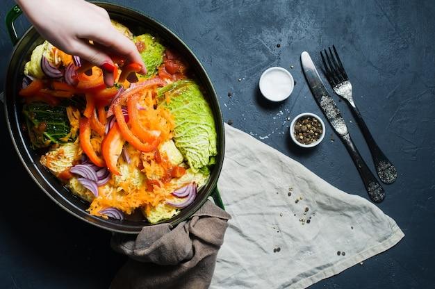 Chefkoch streut zwiebel auf mit fleisch und gemüse gefüllte wirsingrouladen.