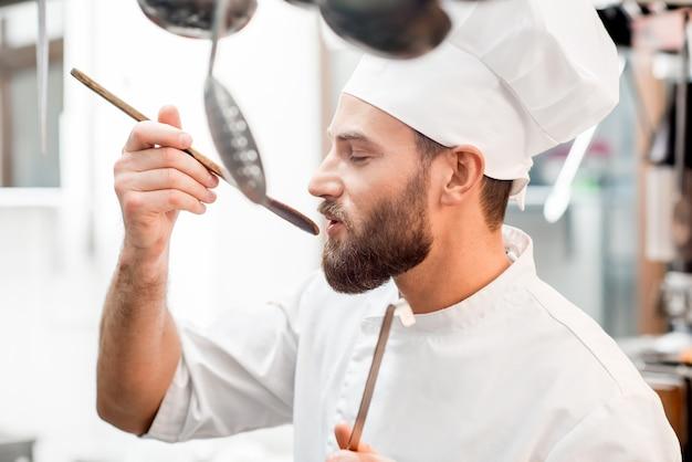 Chefkoch verkostung von speisen mit holzlöffel in der restaurantküche