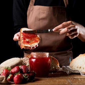 Chefkoch verteilt erdbeermarmelade auf gezüchteten