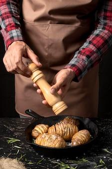 Chefkoch würzt kartoffeln in der pfanne