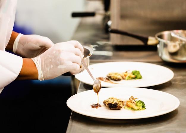 Chefkochen, chef, der lebensmittel zubereitet, chef, der teller in der küche verziert