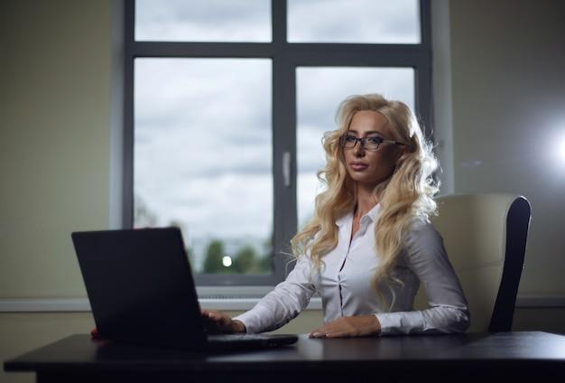 Chefmädchen, das am schreibtisch im büro sitzt und mit laptop arbeitet