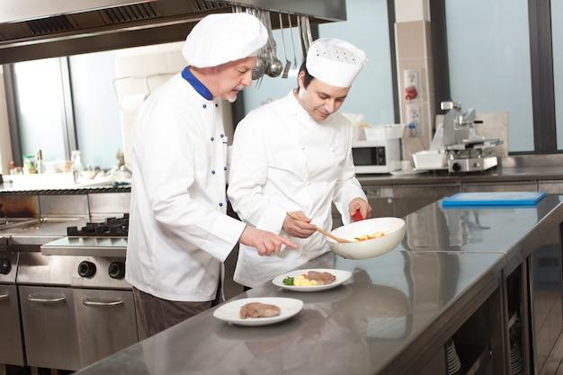 Chefs, die ein teller in einer küche vorbereiten