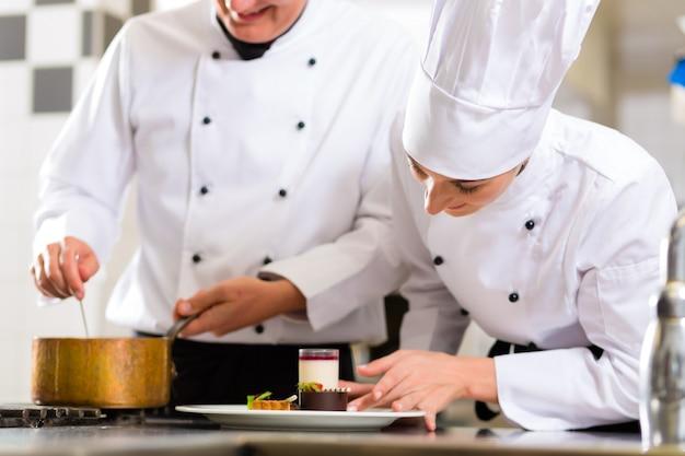 Chefteam in der restaurantküche mit nachtisch