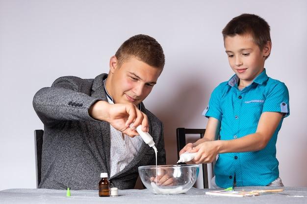 Chemie-ausbildungs- und ausbildungskonzept. nahaufnahme eines jungen und seines vaters, der ein chemisches experiment zu hause durchführt und schleim aus klebstoff, natriumtetraborat und farbstoffen herstellt