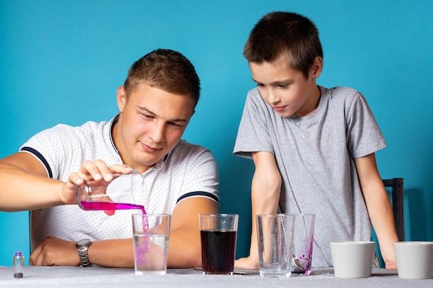 Chemie-ausbildungs- und ausbildungskonzept. nahaufnahme eines jungen und seines vaters, wissenschaftler gießen kaliumpermanganat in ein reagenzglas für ein experiment mit farbwechsel, experimente zu hause