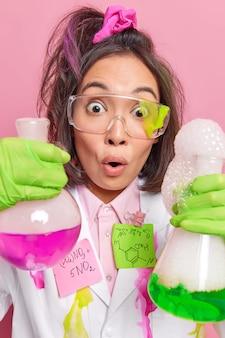 Chemie bereitet tests vor lösung hält zwei glaskolben mit bunter flüssigkeit passt formeln an verwendet verschiedene reagenzien zum testen chemischer reaktionen
