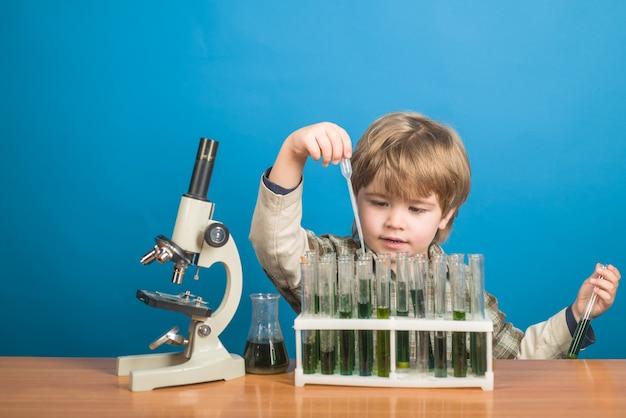 Chemie wissenschaft biologie experiment bildung studienerfolg schulfächer junge mit reagenzgläsern und