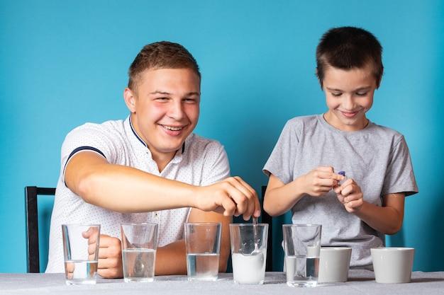 Chemieausbildung und studienkonzept. papa und ihr sohn rühren die mischung mit einem messlöffel in einen behälter mit chemischen elementen, für experimente zu hause