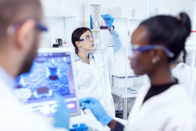 Chemieexperte, der wissenschaftliche probe im geschäftigen labor betrachtet. multiethnisches team medizinischer forscher, die im sterilen labor mit schutzbrille und handschuhen zusammenarbeiten.