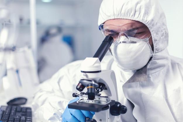Chemieingenieur mit brille, der gesundheitsuntersuchungen am mikroskop durchführt. wissenschaftler im schutzanzug, der während der globalen epidemie am arbeitsplatz mit moderner medizintechnik sitzt.