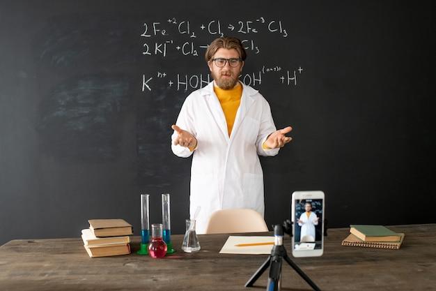 Chemielehrer im weißen mantel, der an der tafel vor dem smartphone steht, während er sich während des online-unterrichts selbst erschießt