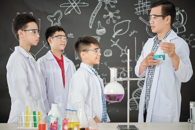 Chemielehrer zeigt becher mit blauer flüssigkeit einer gruppe aufgeregter schüler in schutzbrillen und laborkitteln