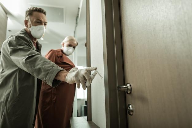 Chemikalien aus dem behälter. mann in professionellen atemschutzmasken, die türhand mit spray bedecken, während sein verbündeter zurückbleibt