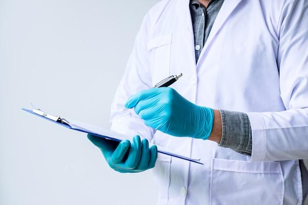Chemiker analysiert probe und notiert im labor mit ausrüstung