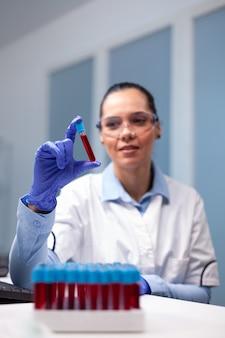 Chemiker-arzt, der dna-blut mit medizinischem vacutainer analysiert, der am mikrobiologie-experiment arbeitet