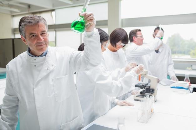 Chemiker, der becher der grünen flüssigkeit aufwirft