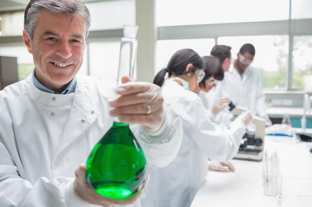 Chemiker, der becher lächelt und hält