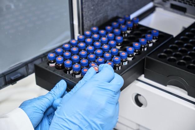 Chemiker, der das fläschchen mit einer probe in den autosampler des hplc-systems gibt.