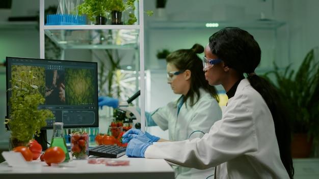 Chemiker, der erdbeere mit organischer dna-flüssigkeit injiziert, während er im pharmazeutischen landwirtschaftslabor arbeitet