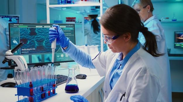 Chemiker, der in einem modern ausgestatteten labor flüssigkeit in ein reagenzglas mit mikropipette einsetzt