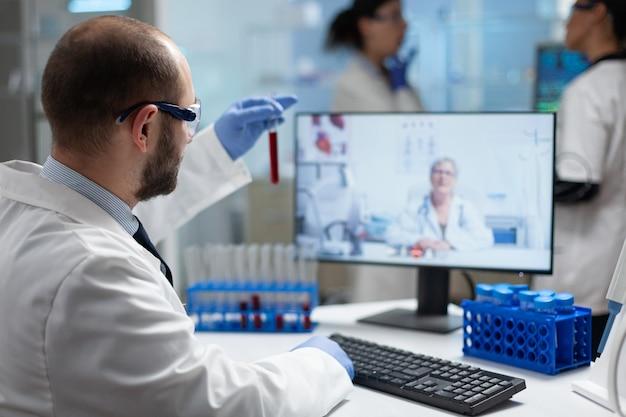 Chemiker, der medizinische reagenzgläser hält, um blutgutachten zu analysieren