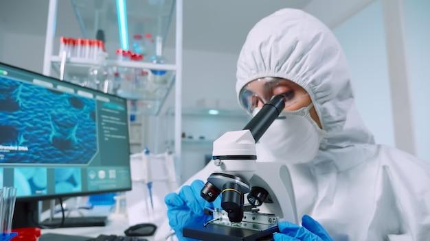 Chemiker, der overall im sterilen labor trägt und experimente für die medizinische industrie mit mikroskop durchführt. ärzte untersuchen die virusentwicklung mit hightech für die impfstoffentwicklung gegen covid19