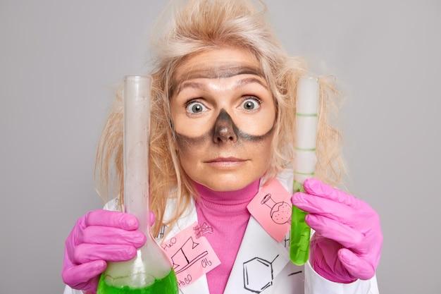 Chemiker ermittler hält glaswaren mit grüner flüssigkeit hat schmutzige spuren um die augen, nachdem er eine schutzbrille getragen hat, sieht überrascht aus. explosion im labor nach durchführung des experiments