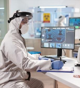 Chemiker-forscher gekleidet in ppe-anzug mit visierschrift auf zwischenablage. untersuchung der impfstoffevolution mit hilfe von hightech-technologie und chemischen werkzeugen für die wissenschaftliche forschung zur virusentwicklung.