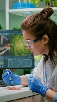 Chemiker injiziert veganes rindfleisch mit einer medizinischen spritze mit protein