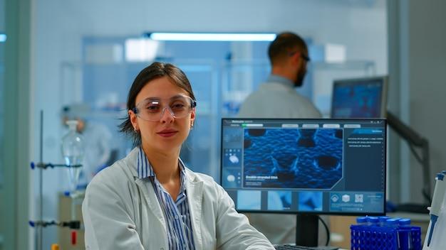 Chemiker mit laborkittel sitzt im labor und schaut lächelnd in die kamera, während kollege im hintergrund am computer arbeitet. wissenschaftler untersuchen die virusentwicklung mit hightech für die wissenschaftliche forschung