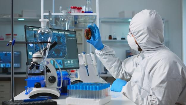 Chemiker mit overall, der bakterienproben aus den typisierungsergebnissen der petrischale analysiert. ärzteteam, das die entwicklung von impfstoffen mit high-tech-chemiewerkzeugen für die erforschung der entwicklung des covid19-virus untersucht