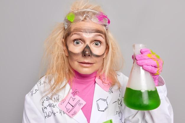 Chemiker mit schmutz um die augen, der von unerwarteten ergebnissen des chemischen experiments betäubt ist, hält glaskolben mit grüner flüssigkeit, die in weißem mantel gekleidet ist, posen im innenbereich. spezialist für biochemie