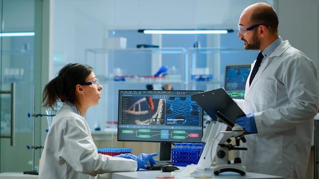 Chemiker-mitarbeiter planen die durchführung eines impfstoffs gegen neue viren in einem modern ausgestatteten labor. chemiker analysieren die evolution mit hightech, um die behandlung gegen covid19 zu erforschen