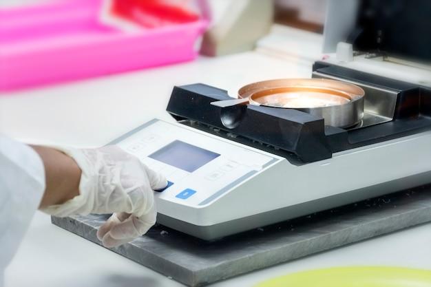Chemiker testet die probe, um feuchtigkeit durch feuchtigkeitsgleichgewicht im chemischen labor zu messen.